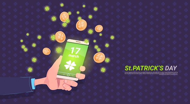 Hand holding smart phone with clover leaf and golden coins over happy st. patricks day background