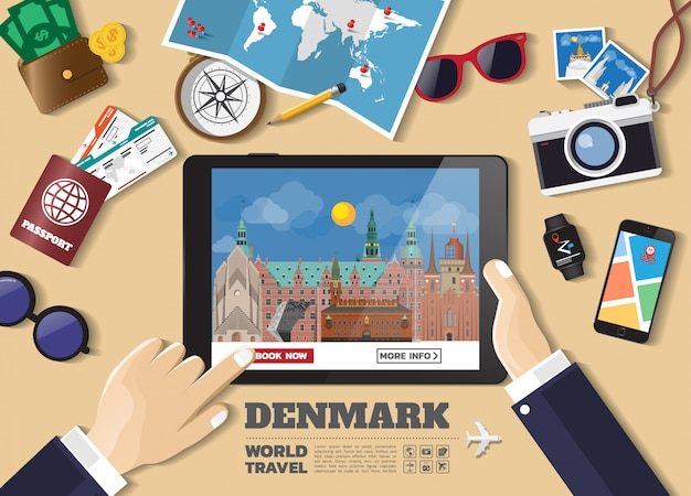 Hand holding smart tablet booking travel destination.denmark famous places
