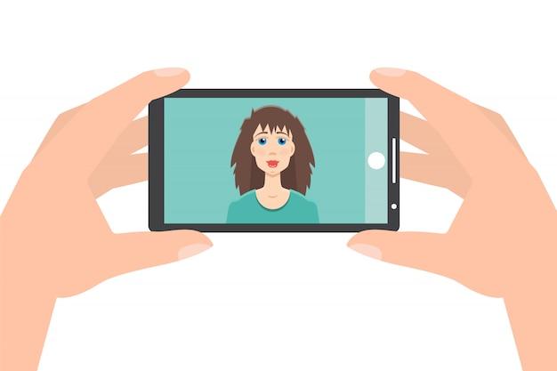 スマートフォンを押しながら写真を撮る手selfie。