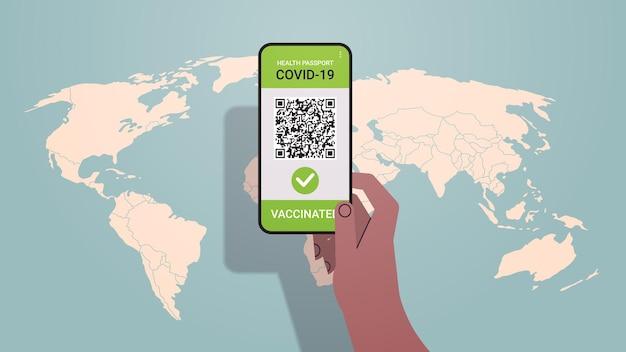 画面にqrコード付きのデジタル免疫パスポートを備えたスマートフォンを手に持つリスクのないcovid-19パンデミックワクチン接種証明書コロナウイルス免疫概念ベクトル図