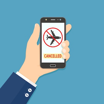 Hand holding smartphone with flight cancelled information