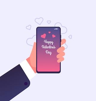 画面に幸せなバレンタインデーのお祝いとスマートフォンを持っている手