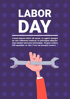 Hand holding spanner labor day holiday background