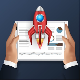 Hand holding tablet with illustration of data analysis and start up rocket launch