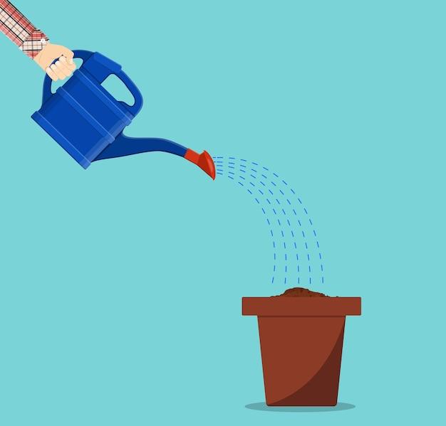 냄비에 물을 수있는 손을 잡고 식물에 물을 수
