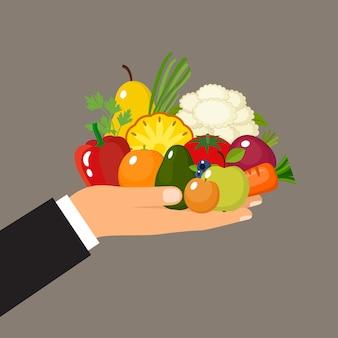Рука держит фрукты и овощи. витамины здоровое питание