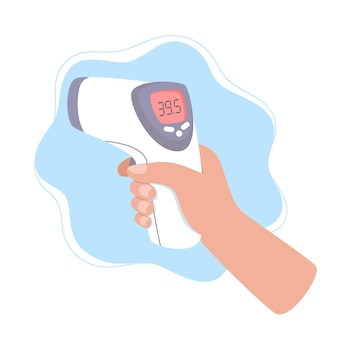 Hand holds an infrared thermometer to measure body temperature