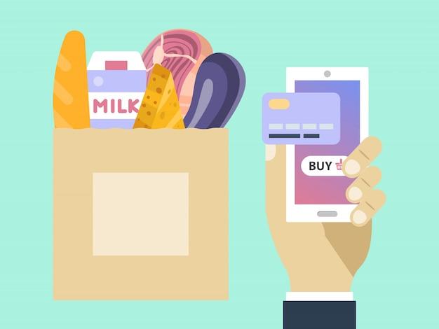 손은 전화 식료품 점을 온라인으로 보유합니다. 음식 온라인 주문 서비스. 식료품으로 가득 찬 종이 봉지. 스마트 폰 및 신용 카드를 들고 남자