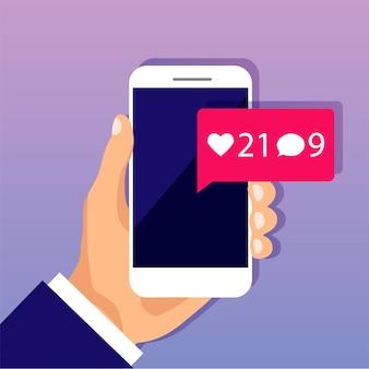 손은 화면에 새로운 소셜 미디어 알림이있는 스마트 폰을 보유하고 있습니다. 채팅 메시지, 좋아요, 하트, 댓글, 팔로워 기호.