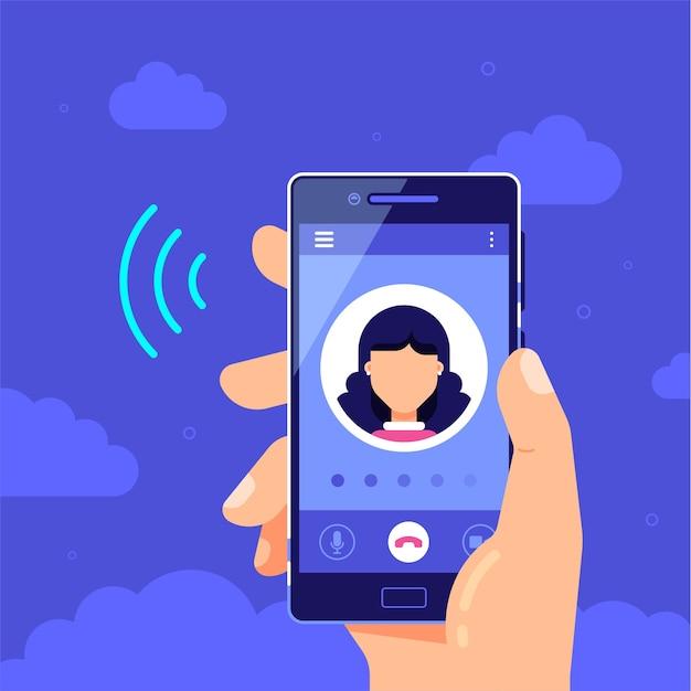 画面に発信通話のスマートフォンを手に持っています。通話サービス。