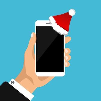 手はサンタの帽子の新年またはクリスマスプレゼントとスマートフォンを保持します