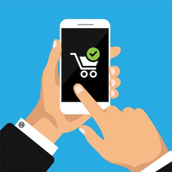 Hand holds smartphone with shop cart on smartphone screen.