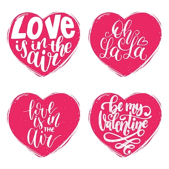Hand lettering phrases love is in the air, oh la la. calligraphy in heart shapes.