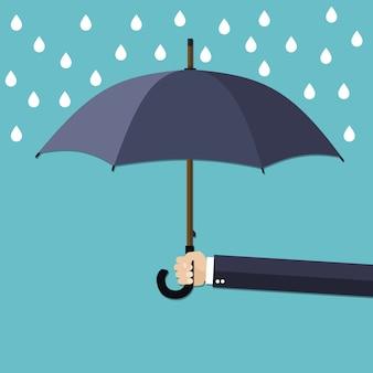 Hand of man holding umbrella under rain.