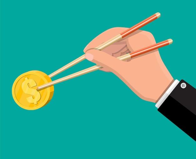 金貨と箸で実業家の手