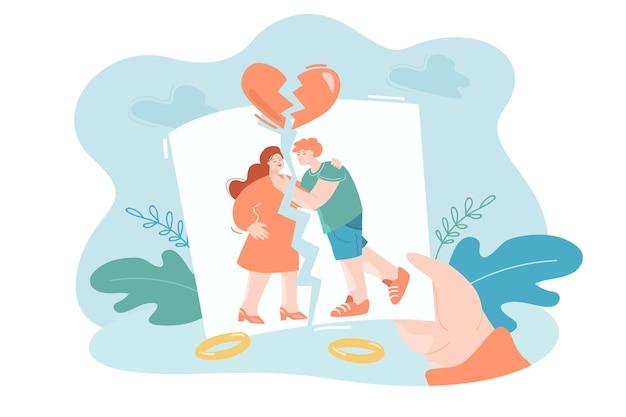 家族の引き裂かれた写真を保持している子供の手家族の離婚の別れの概念