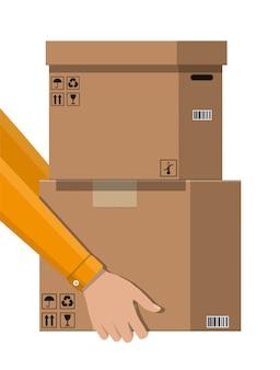 Рука курьера с почтовой картонной коробкой.