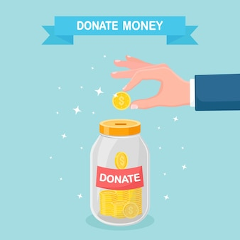 Hand putting coin in glass jar. donate, giving money, charity, volunteering concept. donation box isolated on background