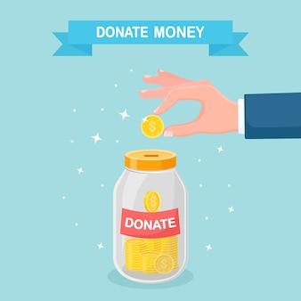 ガラスの瓶にコインを入れる手。寄付、お金の寄付、慈善、ボランティアのコンセプト。背景に分離された寄付ボックス