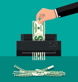 Рука положить долларовую банкноту в шредер.