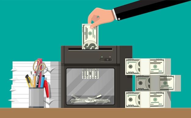 Hand putting dollar banknote in shredder machine.