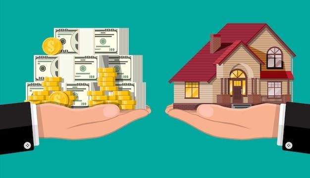 Весы ручные с частным домом и деньгами. покупка дома. недвижимость. пригородный деревянный дом, долларовые стеки и золотые монеты.