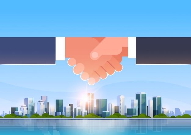 Hand shake over city skyline