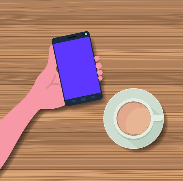Hand using smartphone with coffee cup in the table