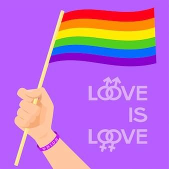 Hand wearing wristband holding rainbow flag