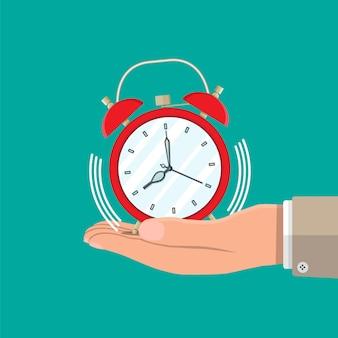 赤い目覚まし時計を持つ手。管理戦略とタスク、時間管理を計画するビジネスプロジェクト、期限。時間管理。ベクトルイラストフラットスタイル