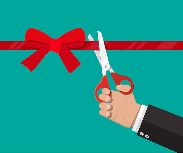 Hand with scissors cut red ribbon