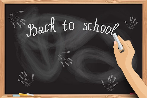 Hand writing at blackboard with chalk inscriptions