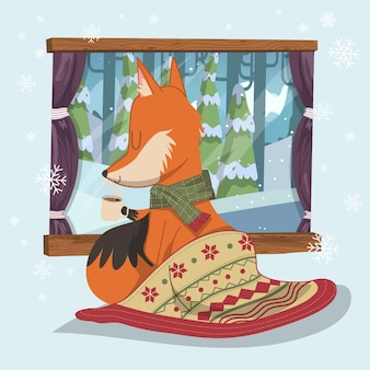 손으로 그린 귀여운 여우는 크리스마스 담요와 초콜릿 한 잔으로 집의 따뜻함을 식히고 있습니다.