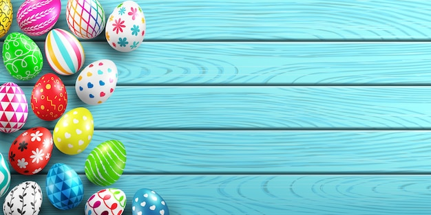 Handmade painted easter eggs on wood background.