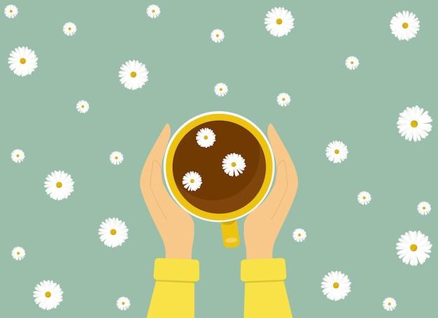 手はカモミールの花のハーブティーの黄色いカップを持っています。ベクトルイラスト。健康と伝統医学の概念