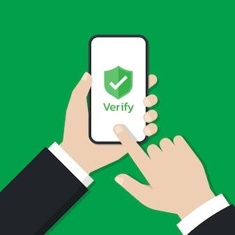 Руки держат смартфон и касаются экрана со значком щита, который отображается на экране.