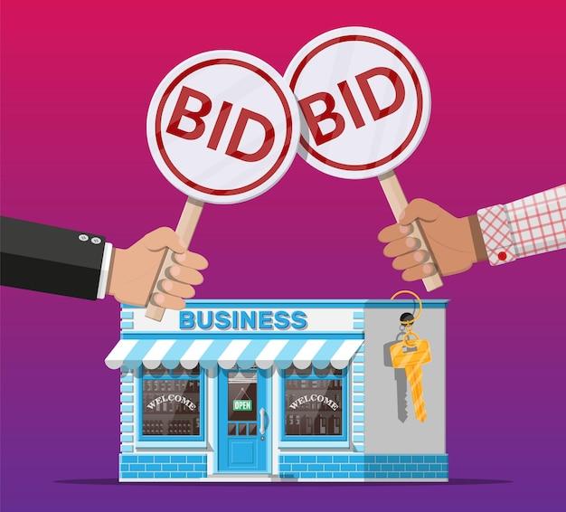 Руки держат аукционное весло. заявочная табличка. недвижимость, домостроительный магазин или коммерческая недвижимость. аукционный конкурс. продажа или покупка нового бизнеса.