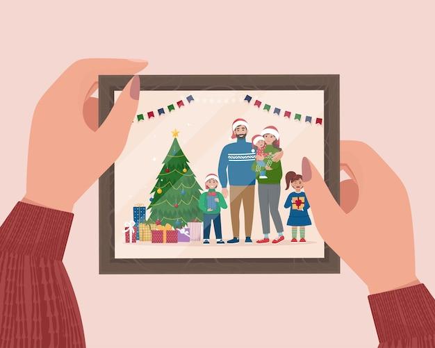 フレームにクリスマスの家族の肖像画を保持している手メモリの写真かわいいフラットベクトルイラスト