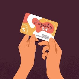 Руки держат пластиковую карту клуба лояльности