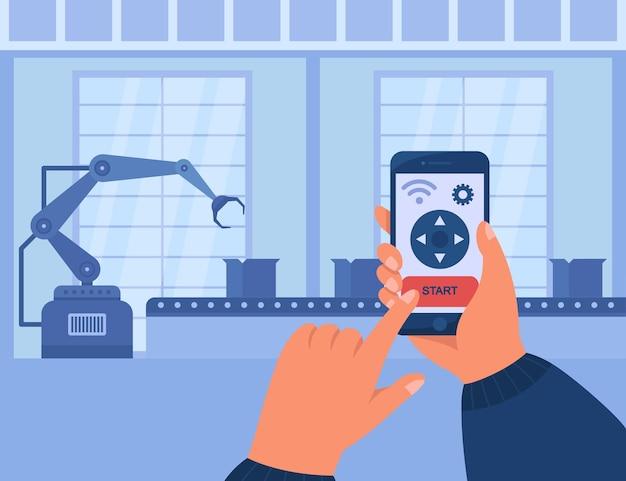 スマートフォンを持ち、アプリを介してコンベアを管理する手。ワイヤレス技術を使用して生産プロセスを制御するエンジニア。工場、産業、povの概念