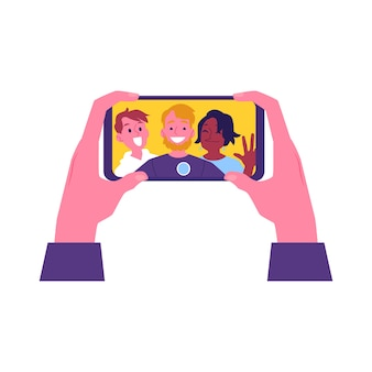 Hands holding smartphone with cheerful friends selfie in screen