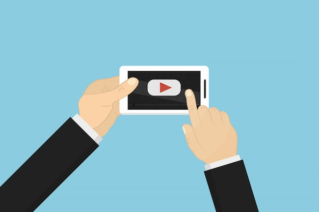 両手で装飾用のビデオが付いている携帯電話を押しながら青色の背景を覆っています。