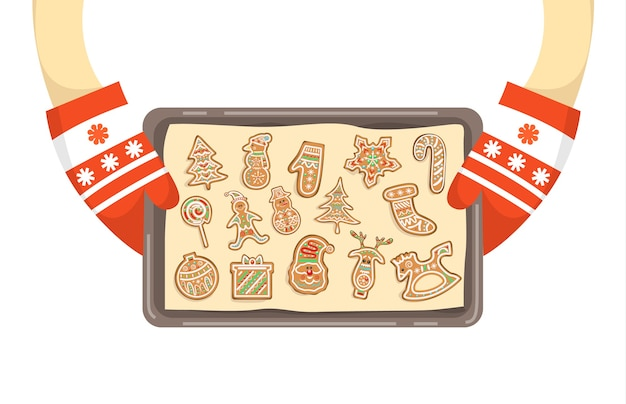 自家製クッキーのトレイを保持している手袋の手。伝統的な休日のジンジャーブレッド。図
