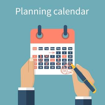 Hands marking calendar