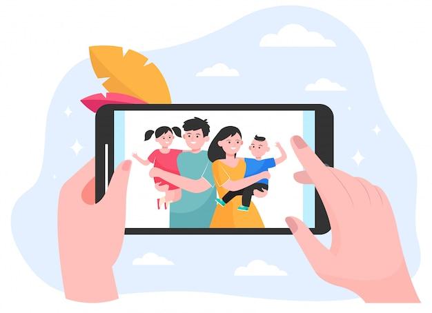 Mani della persona che guardano la foto dei bambini e della famiglia