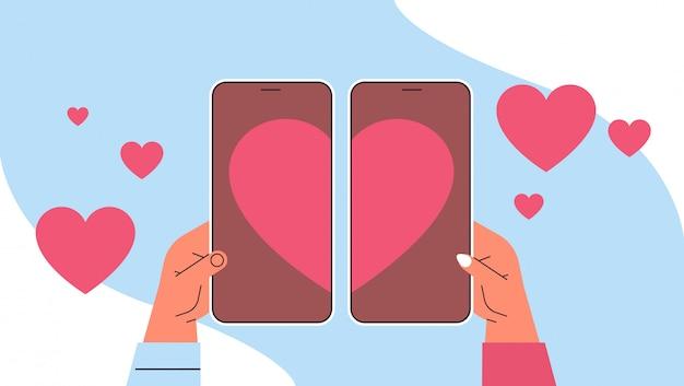 Руки, соединяющие части сердца на экранах смартфонов влюбленная пара использует мобильное приложение для знакомств виртуальная встреча социальные отношения общение горизонтальные