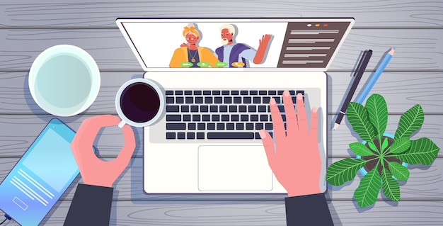Руки с помощью ноутбука в чате с бабушкой и дедушкой во время виртуальной встречи видеозвонок семейный чат концепция онлайн-общения на рабочем месте рабочий стол угол обзора горизонтальный