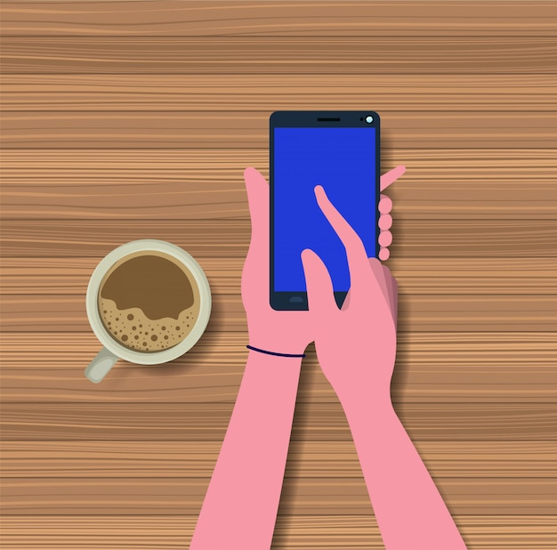 Hands using smartphone with coffee cup in the table