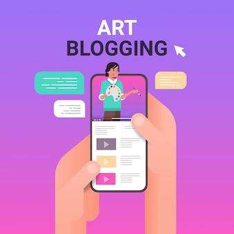 Руки, используя смартфон с художником-блоггером на экране человек-художник, использующий кисть и палитру арт-блогов живая потоковая концепция портрет онлайн мобильное приложение