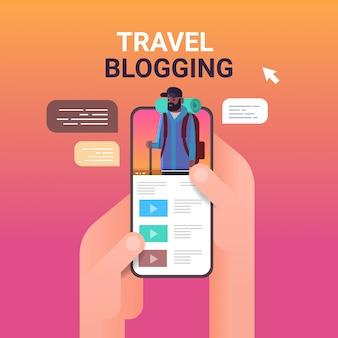 Руки, используя смартфон с путешествия блоггером на экране человек vlogger с рюкзаком пешие прогулки блоги живой потоковой передачи концепция портрета онлайн мобильное приложение